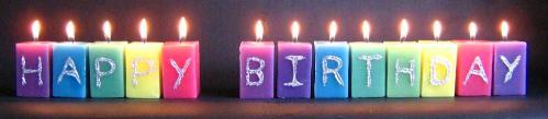 Pink, green, turquoise, purple and yellow square candles spelling out 'HAPPY BIRTHDAY'